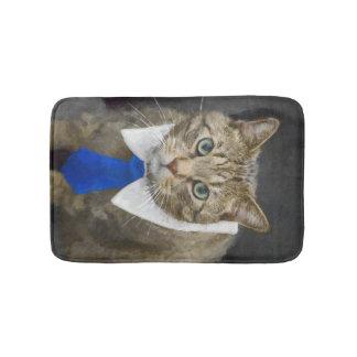 Cute green-eyed brown tabby cat wearing a blue tie bath mat