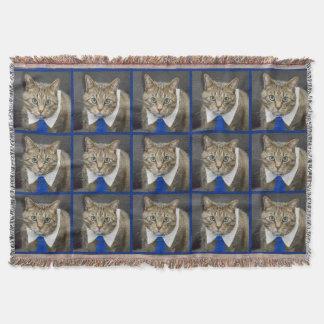 Cute green-eyed brown tabby cat wearing a blue tie throw blanket