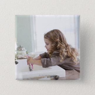 Cute little girl brushing teeth at bathroom sink 15 cm square badge