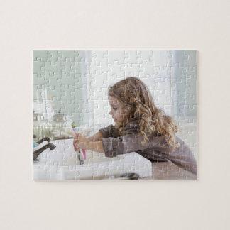 Cute little girl brushing teeth at bathroom sink jigsaw puzzle