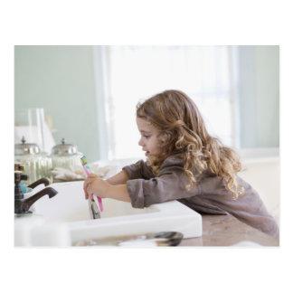 Cute little girl brushing teeth at bathroom sink postcard