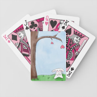 Cute white bunny sitting by a tree bicycle playing cards