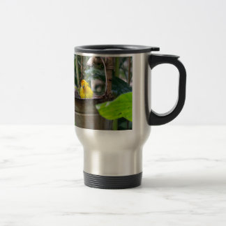 Cute, yellow bird bathing in a bucket stainless steel travel mug