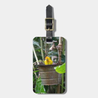 Cute, yellow bird bathing in a bucket tag for bags