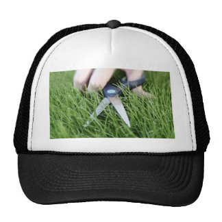 Cutting the grass with a pair of scissors cap