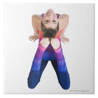 Dancer touching feet to head tiles