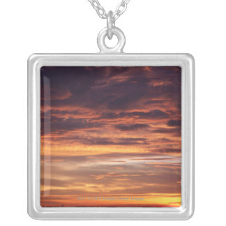 Dark clouds in orange streaked sky silver plated necklace
