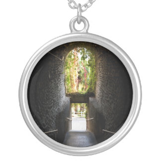 Dark stairs with a stone archway that going down round pendant necklace