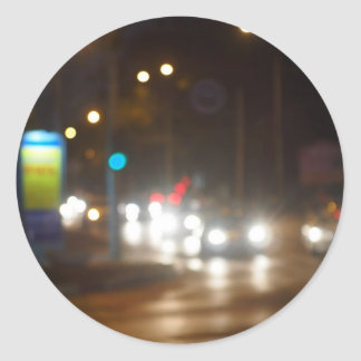 Defocused lights on the stream of cars and traffic round sticker
