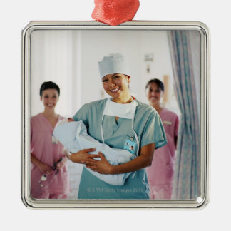 Delivery room nurse holding baby, nurses in christmas ornament
