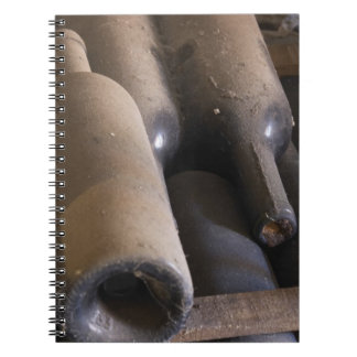 Detail of dusty bottles sur lattes on wooden notebook