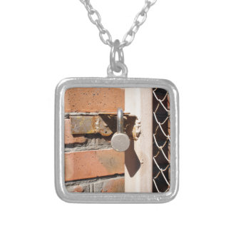 Detail of the gate of the metal mesh that are clos square pendant necklace