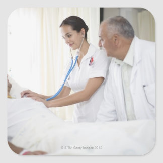 Doctor and nurse tending to patient square sticker
