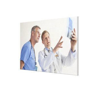 Doctor explaining X-ray to male nurse Canvas Print