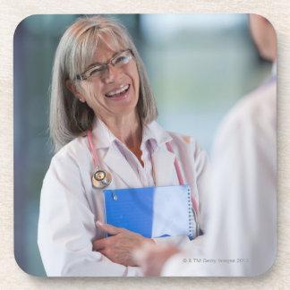 Doctors talking together in hospital hallway coaster