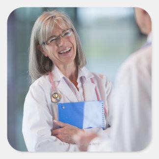 Doctors talking together in hospital hallway square sticker