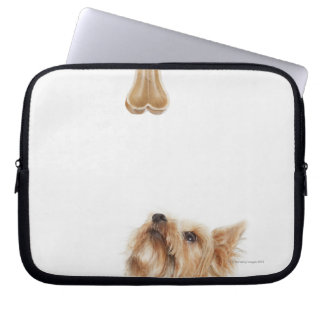 Dog looking up at bone laptop sleeve
