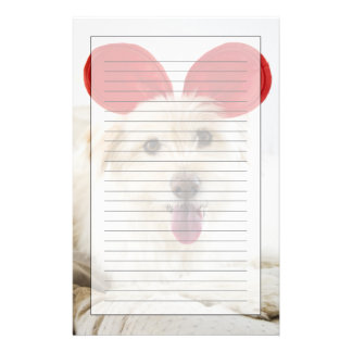 Dog wearing toy ears on bed stationery
