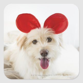 Dog wearing toy ears on bed sticker