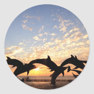 Dolphin's jumping from the water at sunset round sticker