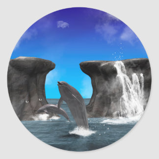 Dolphins swim and jumping in the sea round sticker