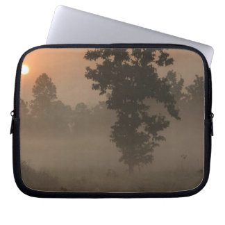 Early morning, rising sun and ground fog laptop sleeve