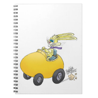 Easter bunny driving an Easter egg, on a notebook. Notebook