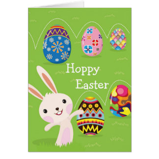 Easter bunny playful with painted eggs greeting card