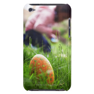 Easter eggs hidden in grass, girl (7-9) in iPod touch cases