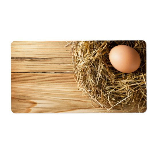 Egg In Hay Nest On Wooden Table Background
