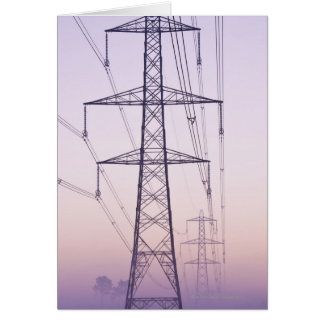 Electricity pylons in mist at dawn. greeting card