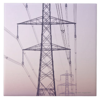 Electricity pylons in mist at dawn. large square tile