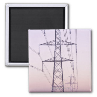 Electricity pylons in mist at dawn. square magnet