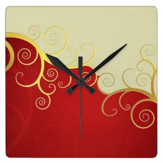 Elegant golden swirls on red and cream wall clocks