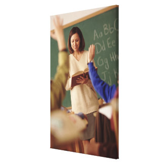 Elementary school students raising their hands canvas print