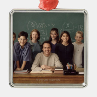 Elementary school students standing behind christmas ornament
