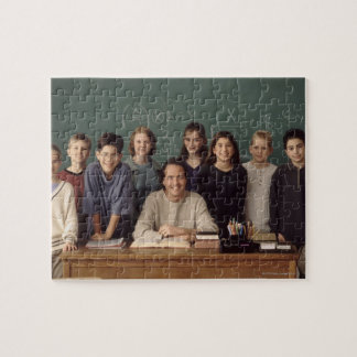 Elementary school students standing behind jigsaw puzzle