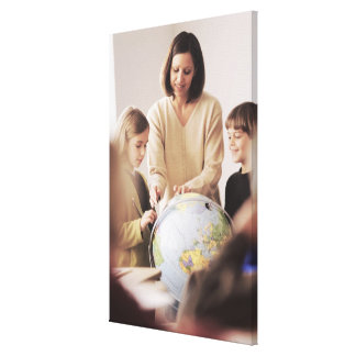 Elementary school teacher showing globe to gallery wrapped canvas