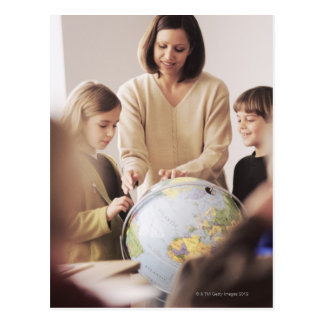 Elementary school teacher showing globe to postcard