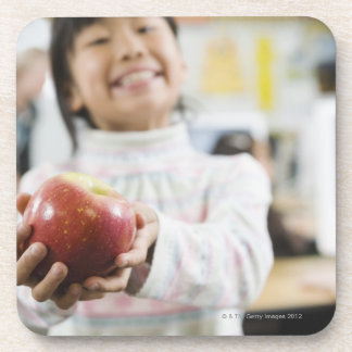 Elementary student holding an apple in her hand coaster