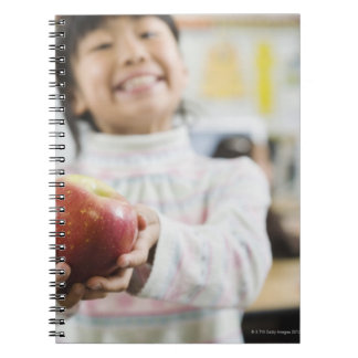 Elementary student holding an apple in her hand notebooks