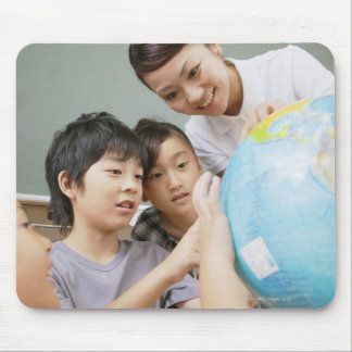 Elementary students and teacher looking at mouse mat