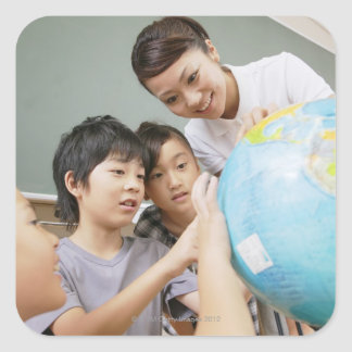 Elementary students and teacher looking at square sticker