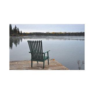 Empty chair on lake deck canvas print