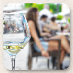 Empty glass from wine and blurred silhouettes beverage coaster