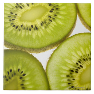 Extreme close-up of four pieces of sliced kiwi tile