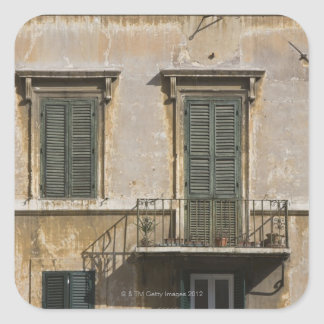 facade of building with a balcony and shuttered square sticker