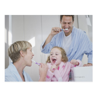 Family brushing teeth together postcard