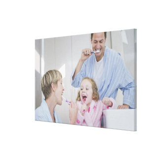 Family brushing teeth together stretched canvas print