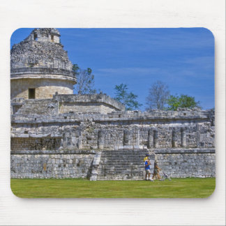 Family of tourists walk past ancient Mayan Mouse Mat